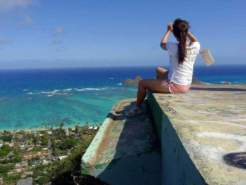 A woman snaps a photograph from atop a pill-box along the Lanikai Pill Box trail in Lanikai, Hawaii, where the Obamas have been hiking. AP Photo