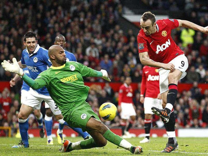 Manchester United's Dimitar Berbatov, right, scores past Wigan's goalkeeper Ali Al-Habsi during their English Premier League soccer match at Old Trafford Stadium in Manchester, England. AP Photo