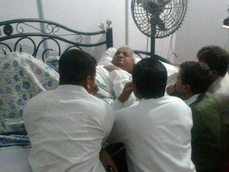 Anti-corruption activist Anna Hazare, surrounded by his associates, rests on a bed after his health deteriorated on the first day of three-day fast at MMRDA ground in Mumbai. PTI Photo
