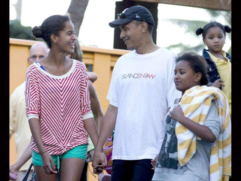 President Barack Obama holds hands with his daughters Malia, left, and Sasha, right, as they leave Sea Life Park, a marine wildlife park, with family friends, in Waimanalo, Hawaii. AP Photo/Carolyn Kaster