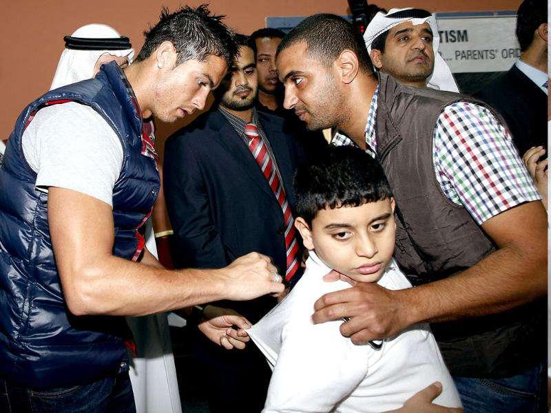 Real Madrid's Cristiano Ronaldo (L) signs an autistic boy's t-shirt during his visit to a autism centre in Dubai. (Reuters)