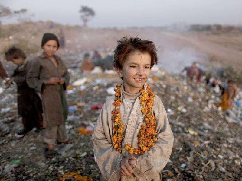 Afghan refugee boy Shafiq Mohammed, 9, smiles while wearing a necklace of flowers he collected from a pile of garbage while he and other children look for items of use, on the outskirts of Islamabad.