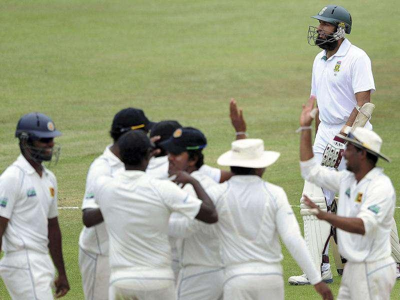 Sri Lankan players celebrate as South Africa's Hashim Amla walks off the field after being run out during their second five-day test in Durban. AP photo