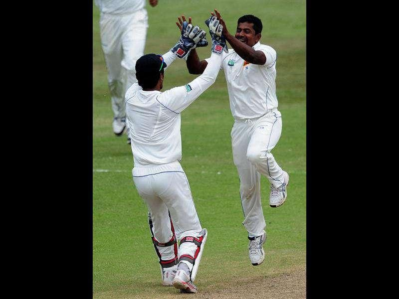 Sri Lanka's Dinesh Chandimal celebrates with Rangana Herath after taking the wicket of South Africa's Jacques Kallis during their second five-day cricket test match in Durban. AP Photo