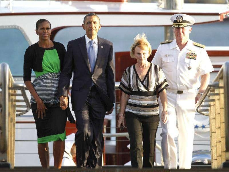 US President Barack Obama (2nd L) and first lady Michelle Obama step aboard the USS Arizona Memorial where they tossed flowers into Pearl Harbor, Hawaii. Accompanying them is Admiral Robert Willard, Commander of the US Pacific Command, and his wife Donna.