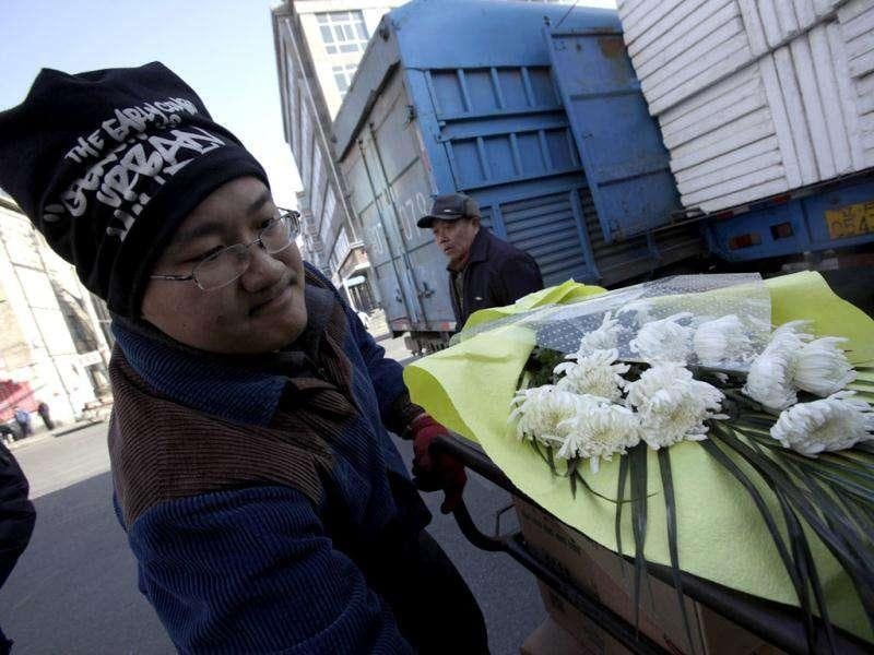 A Chinese man carries a condolence flower to ship to North Korea near the customs office a day after of a memorial service for the late North Korean leader Kim Jong Il, in Dandong, a Chinese city bordering with North Korea.