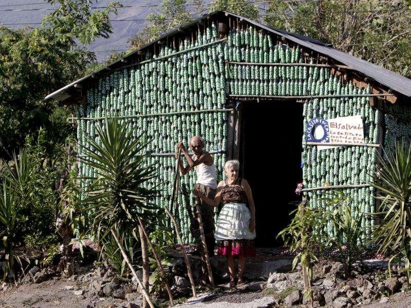 Prudencio Amaya, 102, and his companion Maria Ponce, 78, stand in front of their home's facade, constructed from recycled plastic bottles, near El Transito, El Salvador. Ponce, who did not have money to build a traditional house, says in 2005 that a dream revealed to her to fashion a home from plastic bottles, which took 3 months. The couple survive on about 10 dollars a week which they make from their corn crop and donations from tourists making the journey to see