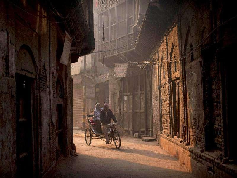 A man pedals a rickshaw carrying a passenger in the old parts of Delhi.