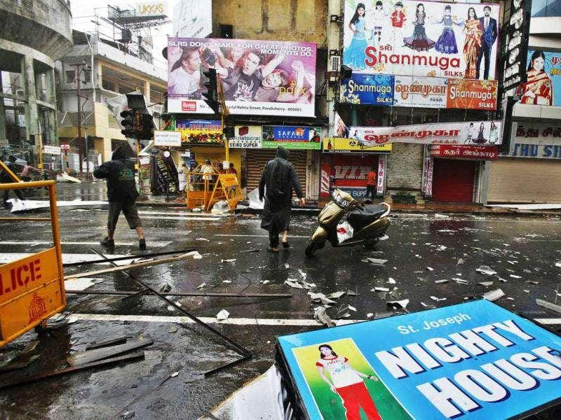 People walk past fallen sign boards and the trash caused by heavy winds in Pondicherry. AP Photo/Aijaz Rahi