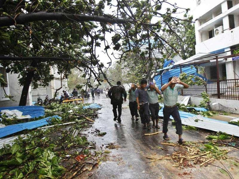 People walk past fallen trees as they run for cover from heavy rain in Pondicherry. AP Photo/Aijaz Rahi