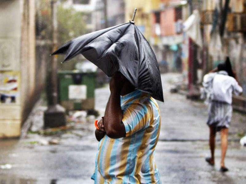 A man stands with an umbrella during heavy winds in Pondicherry. AP Photo/Aijaz Rahi