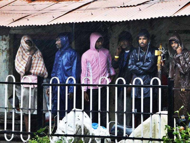 People take shelter during heavy rain and wind in Pondicherry. AP Photo/Aijaz Rahi