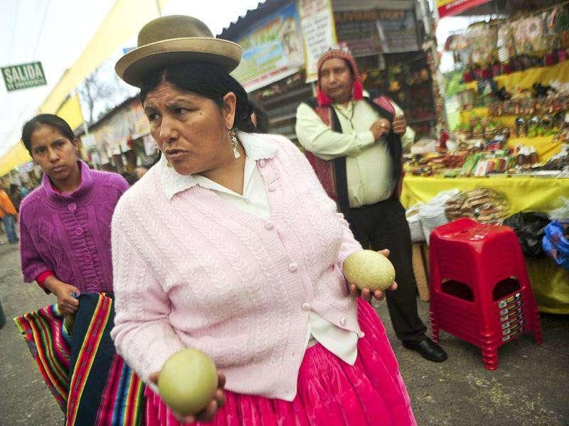 An Andean woman carries ostrich eggs to be used in a ritual of predictions at the Wishes Market in Lima. AFP