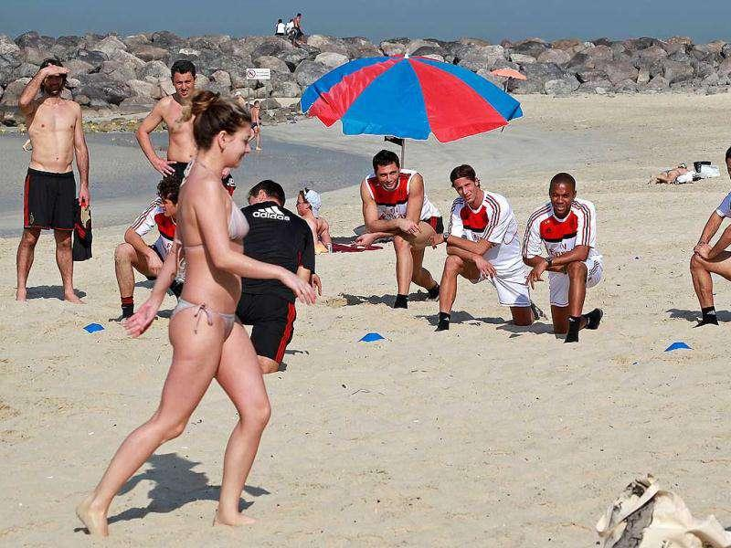 A woman walks past AC Milan players stretching during a training session at Al-Mamzar Beach in the Gulf emirate of Dubai. The Italian champions will face Qatar-backed French club Paris Saint-Germain in the Challenge Cup on January 4, 2012. AFP PHOTO