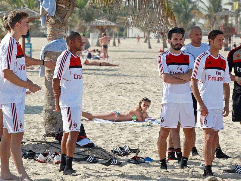 AC Milan players wait for the start of a training session at Al-Mamzar Beach in the Gulf emirate of Dubai. The Italian champions will face Qatar-backed French club Paris Saint-Germain in the Challenge Cup on January 4, 2012. AFP PHOTO
