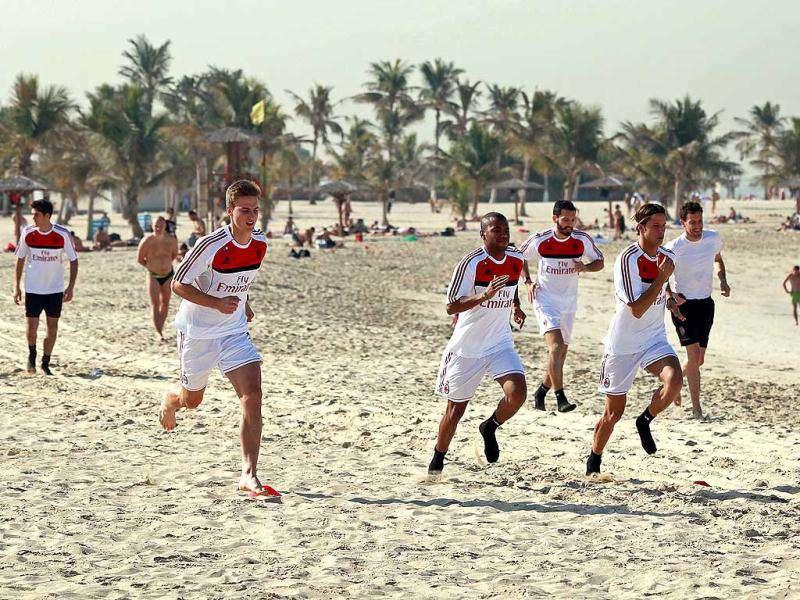 AC Milan players run during a training session at Al-Mamzar Beach in the Gulf emirate of Dubai. The Italian champions will face Qatar-backed French club Paris Saint-Germain in the Challenge Cup on January 4, 2012. AFP PHOTO