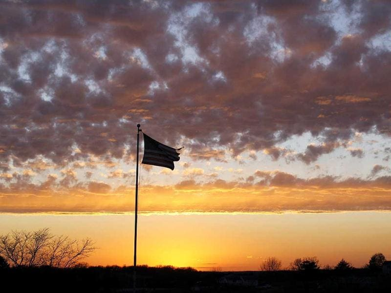 A tattered American flag flies at sunset over a military veterans' cemetery outside of Knoxville, Iowa. Reuters