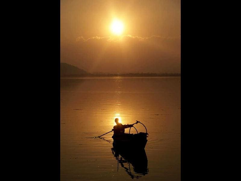 A Kashmiri fisherman rows his boat on the Dal Lake as the sun sets in Srinagar. AP Photo