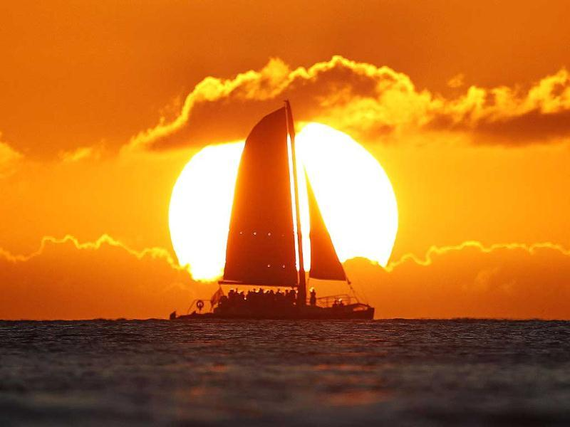 A sail boat passes in front of the sun as the last rays of sunlight of 2011 hit the waters off Waikiki Beach in Honolulu, Hawaii. Reuters