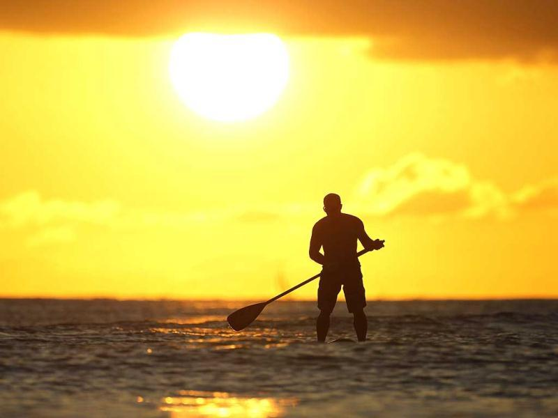 A paddle board rider surfs at sunset on New Year's Eve at Waikiki Beach in Honolulu, Hawaii. Reuters