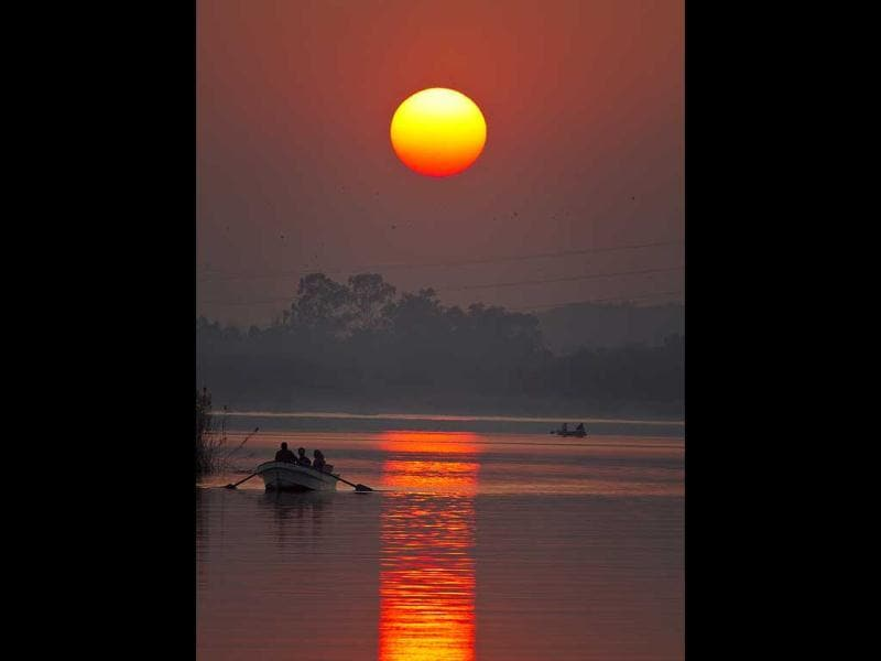 Pakistani tourists enjoy a boat ride on Rawal lake as the sun sets in Islamabad, Pakistan. AP