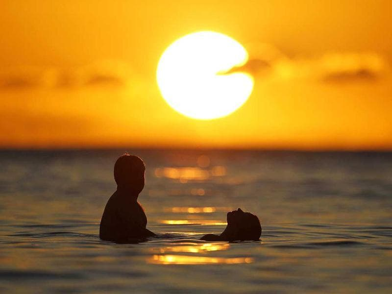 A couple watches the last rays of sunlight for 2011 at sunset from the waters off Waikiki Beach in Honolulu, Hawaii. Hawaii is one of the last places on earth that will usher in the New Year. Reuters