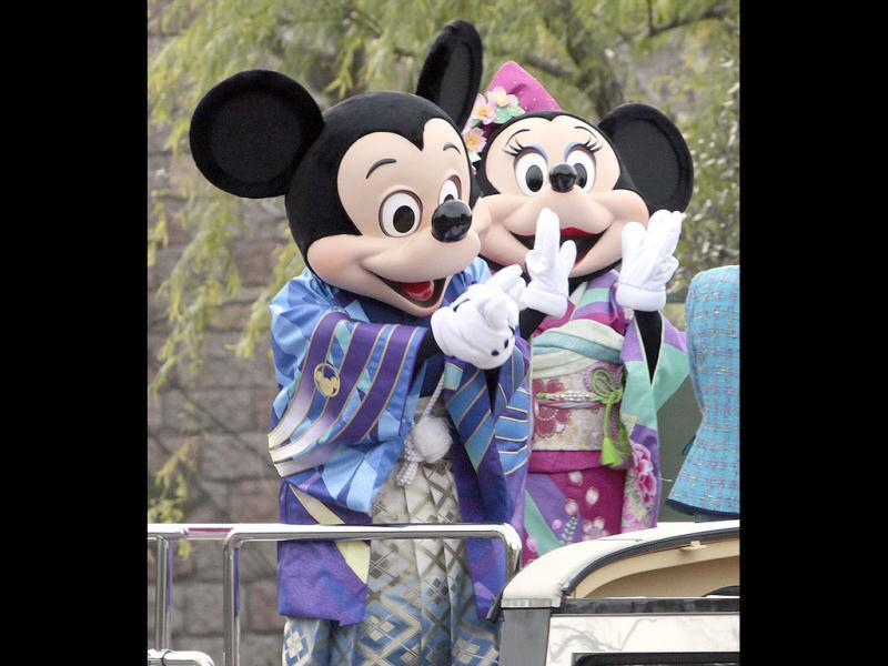 Disney characters Mickey (L) and Minnie Mouse (R), dressed in traditional Japanese kimonos wave to greet guests from a chauffer driven limousine during the theme park's annual New Year's Day parade at Tokyo Disneyland in Urayasu city, suburban Tokyo. Thousands of people visited the theme park to mark the start of the New Year's holiday, the biggest one of the year in Japan. AFP Photo / Yoshikazu Tsuno