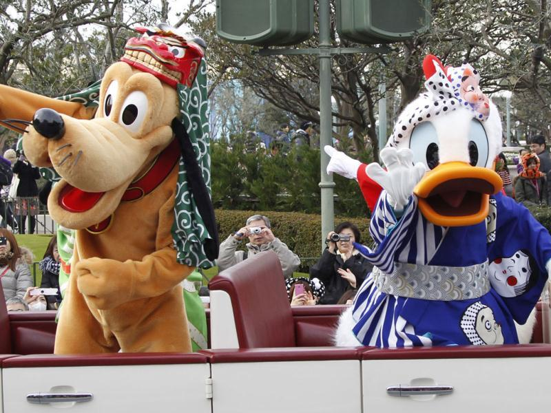 Pluto, left, and Donald Duck acknowledge the visitors and guests during the annual new year's Disney characters' parade at Tokyo Disneyland in Urayasu, near Tokyo, Japan. AP Photo/Koji Sasahara