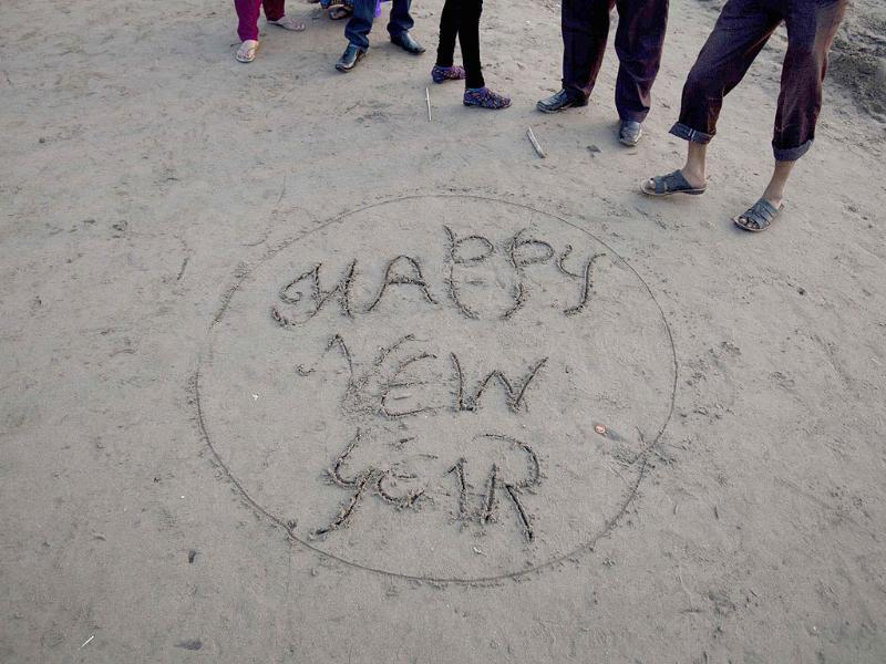 People stand next to a New Year message written in sand at Juhu Beach in Mumbai. Reuters Photo