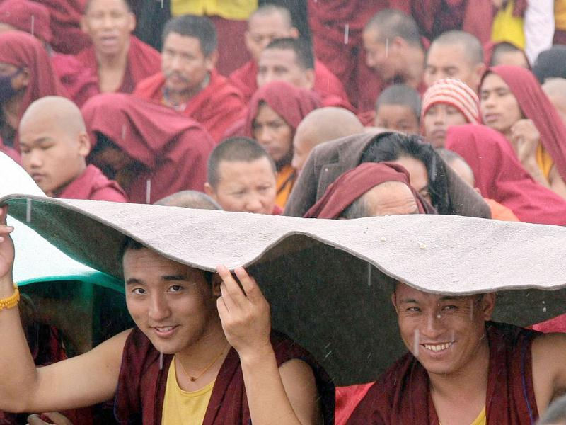 Buddhist monks take shelter from the rain during a teaching session being addressed by the Tibetan spiritual leader the Dalai Lama on the first day of the Kalachakra festival in Bodhgaya. Reuters Photo