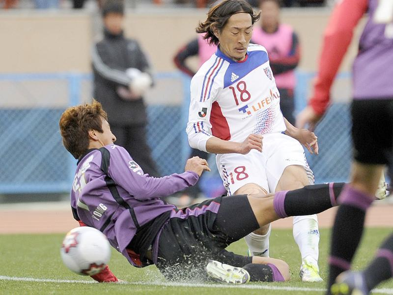 FC Tokyo midfielder Naohiro Ishikawa (C) shoots the ball past Kyoto Sanga FC midfielder Jung Woo-Young during the 91st Emperor's Cup football final in Tokyo. AFP Photo