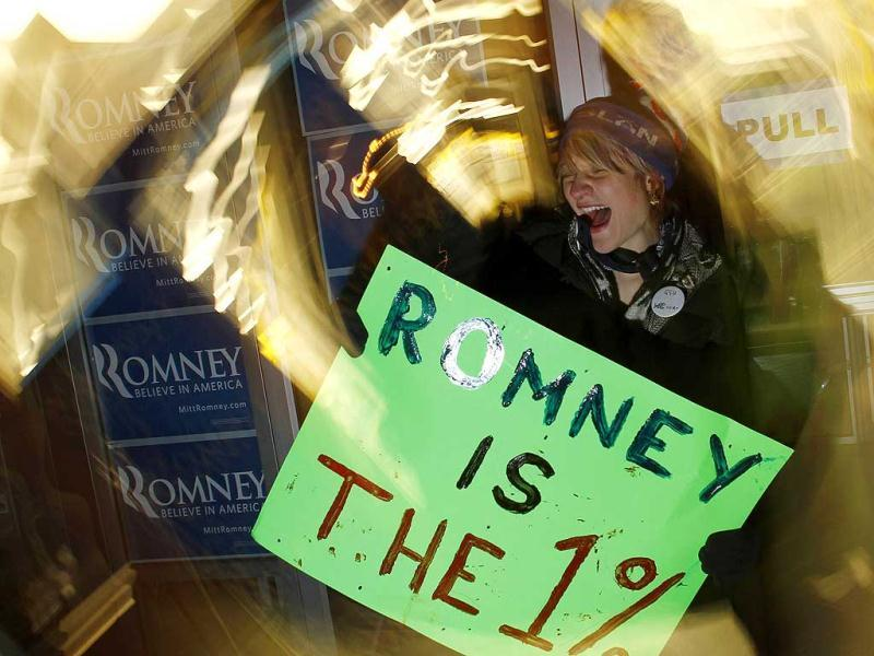A protester yells with a placard outside Republican presidential candidate and former Massachusetts Governor Mitt Romney's office in Des Moines, Iowa.