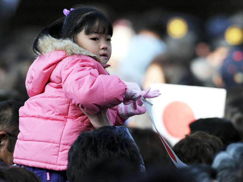 A girl holds the national flag on the shoulder of her father while awaiting for the apperance of royal family at the Imperial Palace in Tokyo. Emperor Akihito and his family greeted well-wishers in customary New Year public apperances.