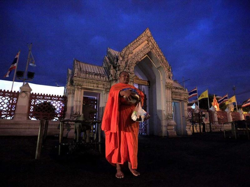A Thai Buddhist monk, holding a bowl for morning alms, stands in front of Marble temple in Bangkok, Thailand to wait for alms offering.