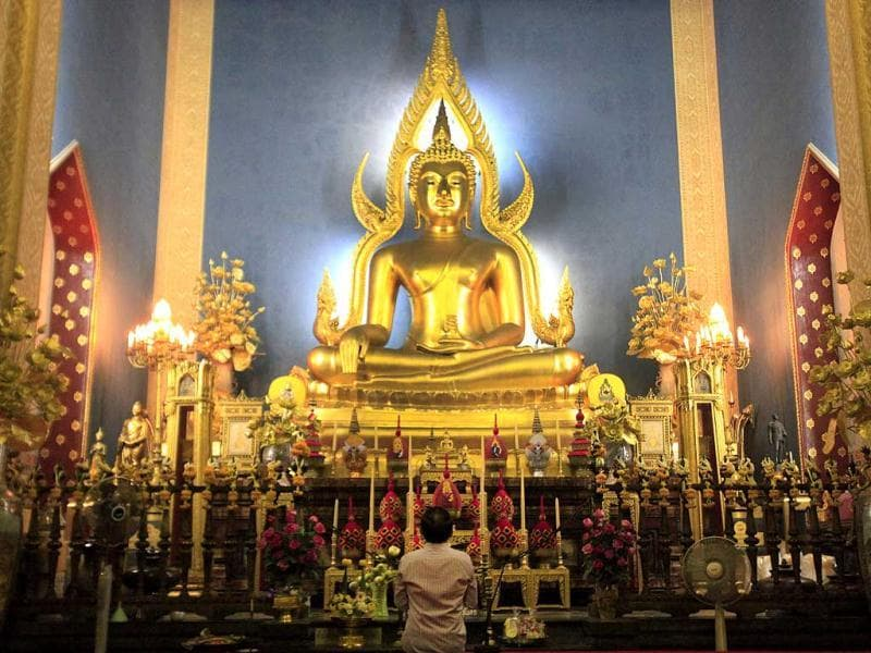 A Thai Buddhist prays in front of a giant Buddha statue at Marble temple in Bangkok, Thailand.