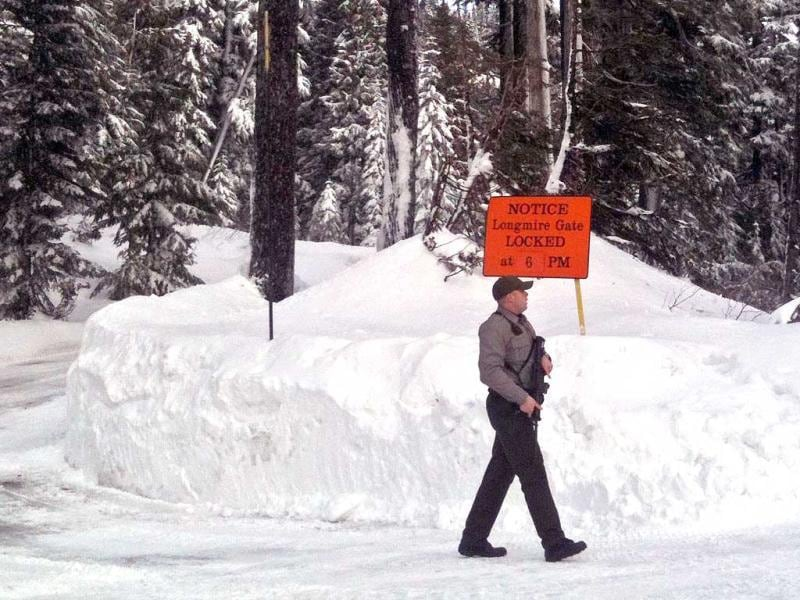 A park ranger holding a rifle patrols the area at Narada Falls in Mount Rainier National Park. A Mount Rainier Park Ranger was shot and killed while attempting to stop a man in a car who was speeding on the road between Paradise and Longmire.