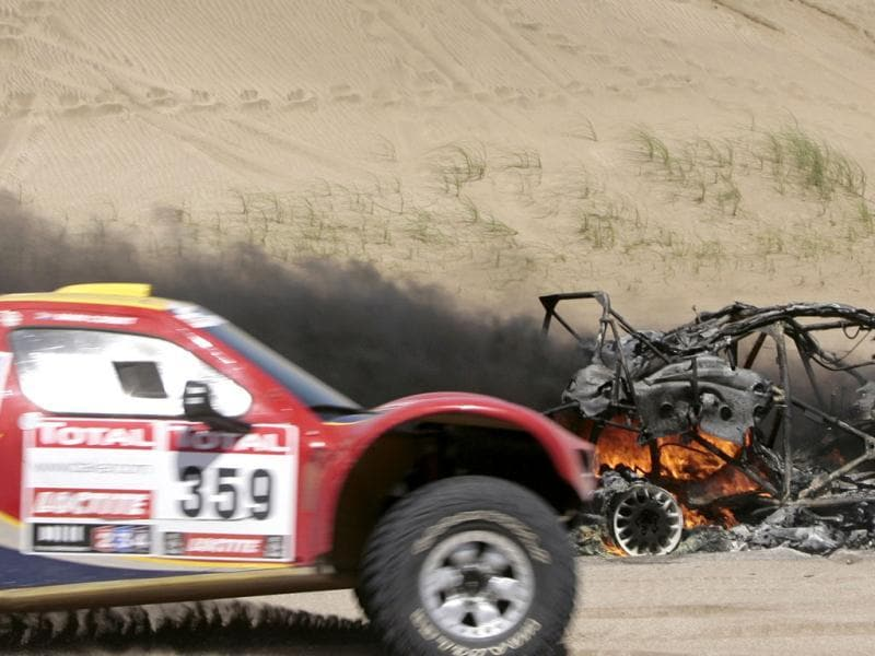 Driver Mark Corbett and co-driver Francois Jordaan, both from South Africa, race their Century Racing car past a burning Volvo car during the first stage of the 2012 Argentina-Chile-Peru Dakar Rally between Mar del Plata and Santa Rosa de la Pampa, Argentina.