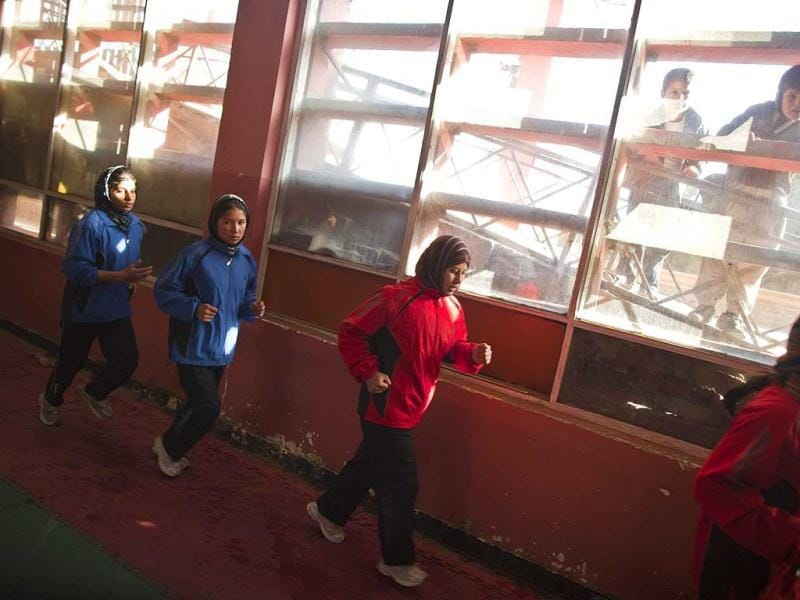 Afghan women boxers run during a practice session as boys watch from outside a boxing club in Kabul. Female boxing is still relatively unusual in most countries, but especially in Afghanistan, where many girls and women still face a struggle to secure an education or work, and activists say violence and abuse at home is common. REUTERS