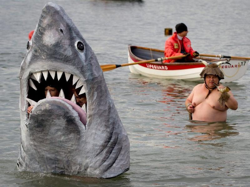 Participants dressed in a shark costume take to the frigid waters of English Bay during the 92nd annual Polar Bear Swim in Vancouver, B.C. (AP Photo/The Canadian Press, Darryl Dyck)