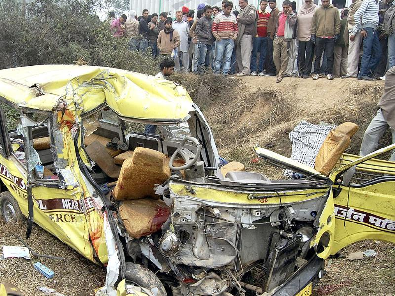 People look at the ill-fated school bus which collided with a truck in Ambala claiming 12 lives. PTI Photo