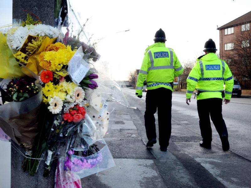 Police officers walk past flowers left at the scene of the murder in Salford, north-west England. Anuj Bidve was gunned down on Dec 26. AFP/Paul Ellis