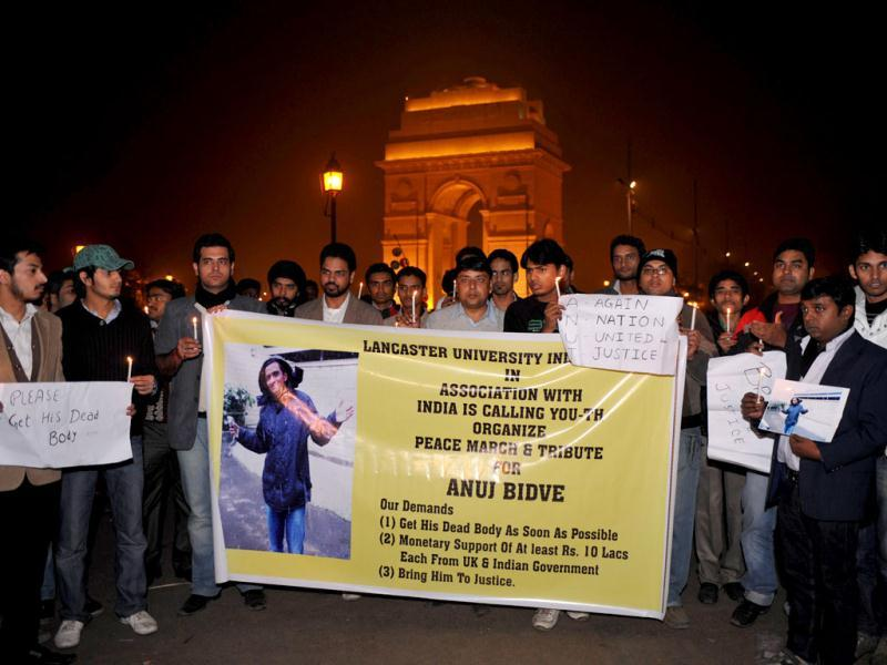 Friends of slain Anuj Bidve pose with a banner and candles during a rally near India Gate in New Delhi. A man describing himself as