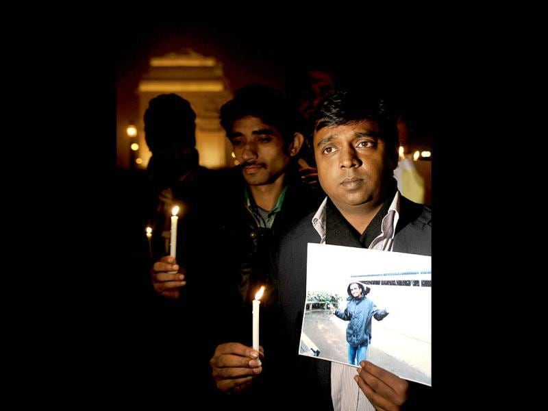 Friends of slain Anuj Bidve hold candles and photographs as they stage a rally near India Gate in New Delhi. A man describing himself as