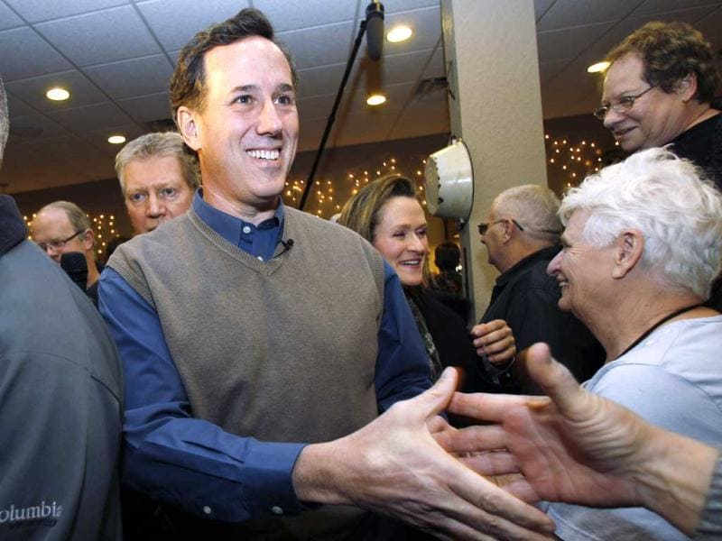 Republican presidential candidate former Pennsylvania Sen. Rick Santorum shakes hands during a meet and greet campaign stop at Pizza Ranch, in Altoona, Iowa. AP