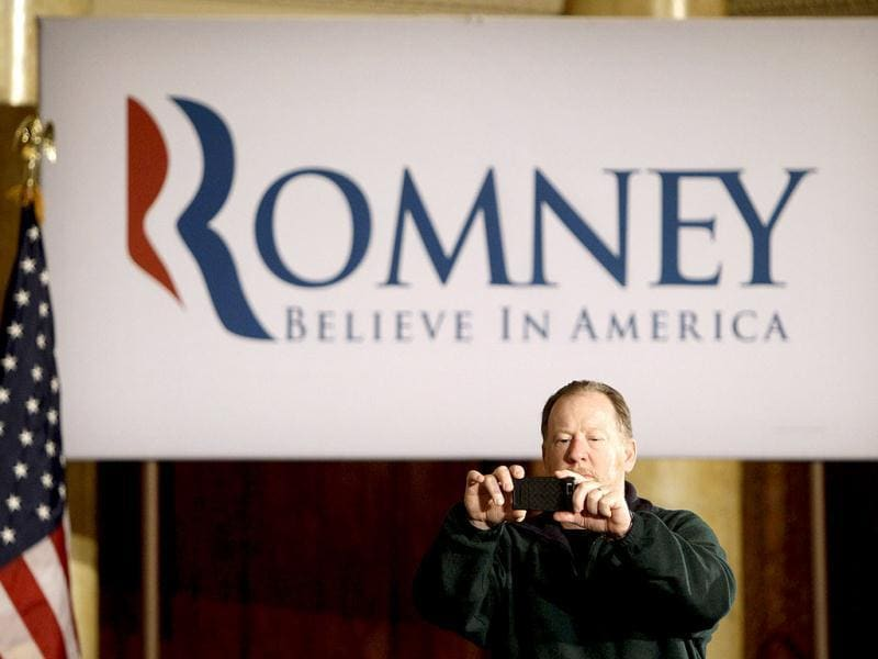 Bob Schrage of Rabbit Hash, Ky., takes a photo as he waits for Republican presidential candidate, former Massachusetts Governor Mitt Romney to speak at a caucus day rally at the Temple for Performing Arts in Des Moines, Iowa. AP Photo/Charlie Neibergall