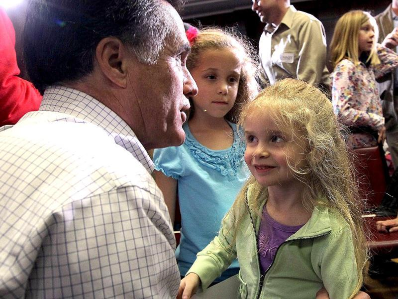 Former Massachusetts governor Mitt Romney greets a young supporter during a campaign stop in Council Bluffs, Iowa. With two days before the Iowa caucuses, Mitt Romney is continuing his bus tour through Iowa. Justin Sullivan/Getty Images