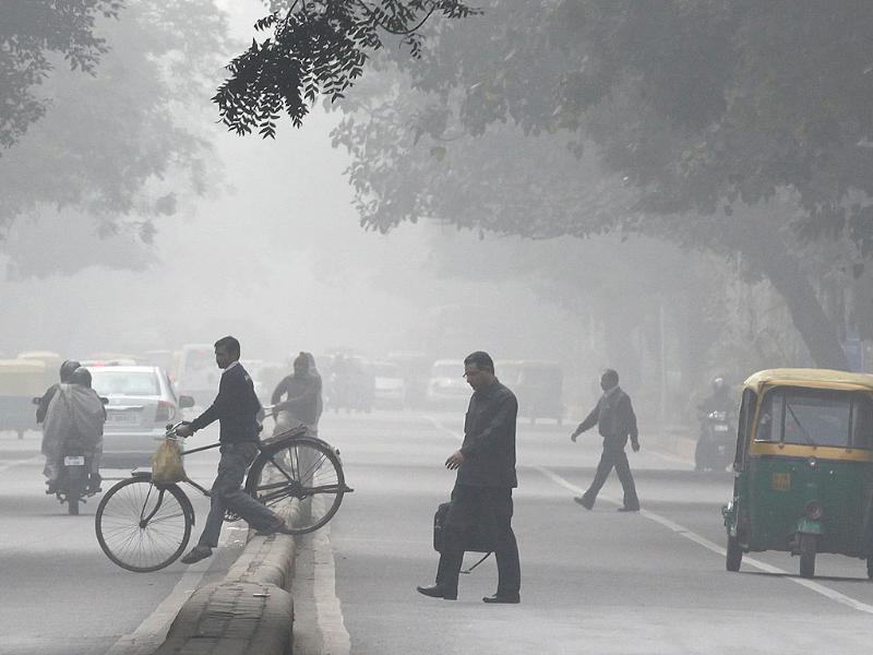 Pedestrians and cyclists cross by violating traffic rules during a foggy day in Connaught Place as Delhi traffic police observe road safety week in the capital. HT Photo/Raj K Raj