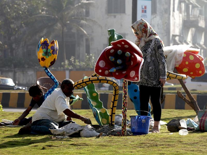 Workers give finishing touches to the beautification of a traffic island at Worli by the BMC, hours after the Model code of conduct was imposed. HT Photo/Kunal Patil