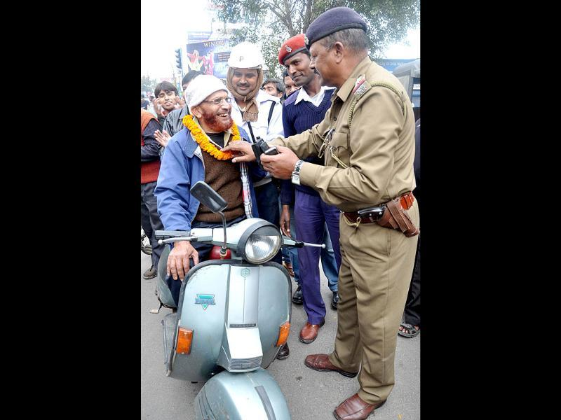 A scooterist without a helmet being garlanded as part of a new drive by Ranchi Police to create awareness among commuters to obey traffic rules at all the important crossroads, in Ranchi.