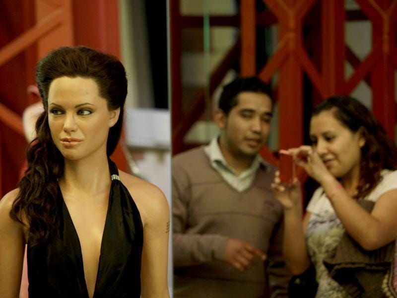 A woman takes a picture of a wax figure, left, depicting actress Angelina Jolie at Mexico City's wax museum Tuesday Jan. 3, 2012. The wax figures of Jolie and her husband actor Brad Pitt are the latest additions to the museum. (AP Photo)